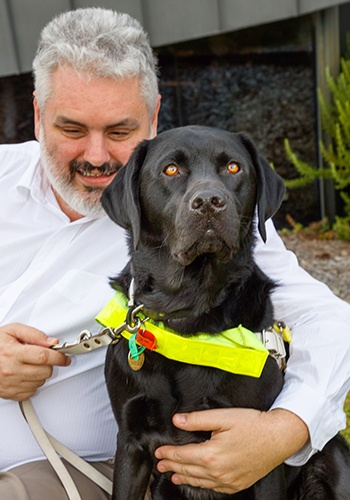Barry cuddles black labrador, Guide Dog Pluto, who sits in harness