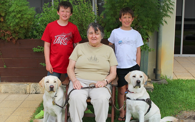 Jean sits and on either side of her are two of her grandsons and her sponsored dogs, Tom and Harry