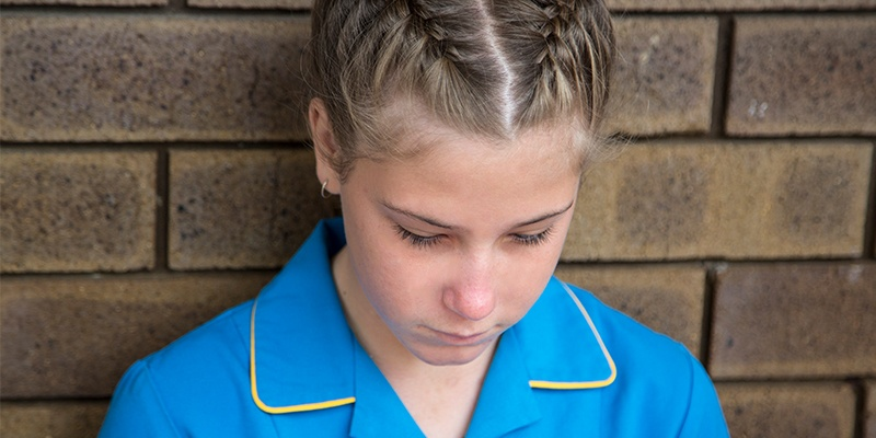 Tegan sits against a brick wall in her school uniform and looks down, sadly
