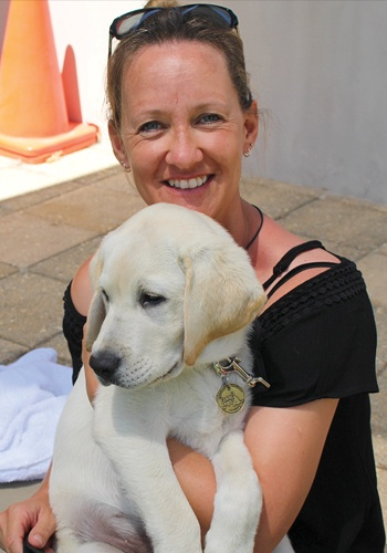 Puppy Raiser Jo smiles at the camera as she cuddles Simba at Puppy Class