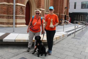 Two women in orange t-shirts are with a black labrador standing on the street with a plastic dog-shaped collection box