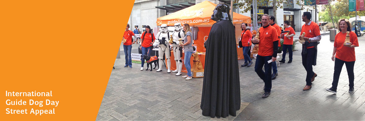 Star Wars Stomtroopers and Darth Vader stand in street with other people in orange t-shirts