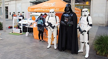 Star Wars characters, Storm Troopers and Darth Vader stand by the Guide Dogs WA merchandise stall