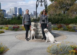 Leonora Flower & Victoria Wilkinson stand with two yellow labradors in Kings Park