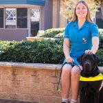 Tegan sits on the edge of a garden bed, with Guide Dog Loui at her feet
