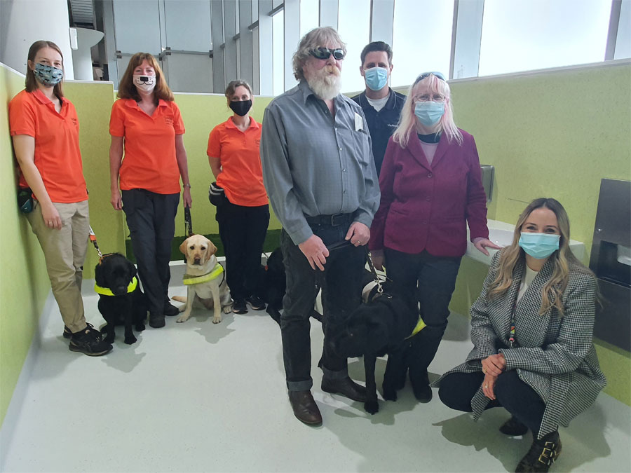 People and dogs in training inside the new service animal relief area at the Perth Airport.