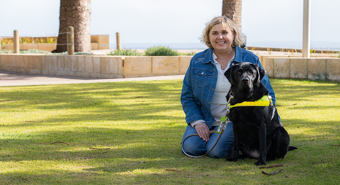 Handler and black Guide Dog sitting on grass.