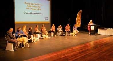 5 graduates and their Guide Dogs and trainers on the stage at the Graduation.